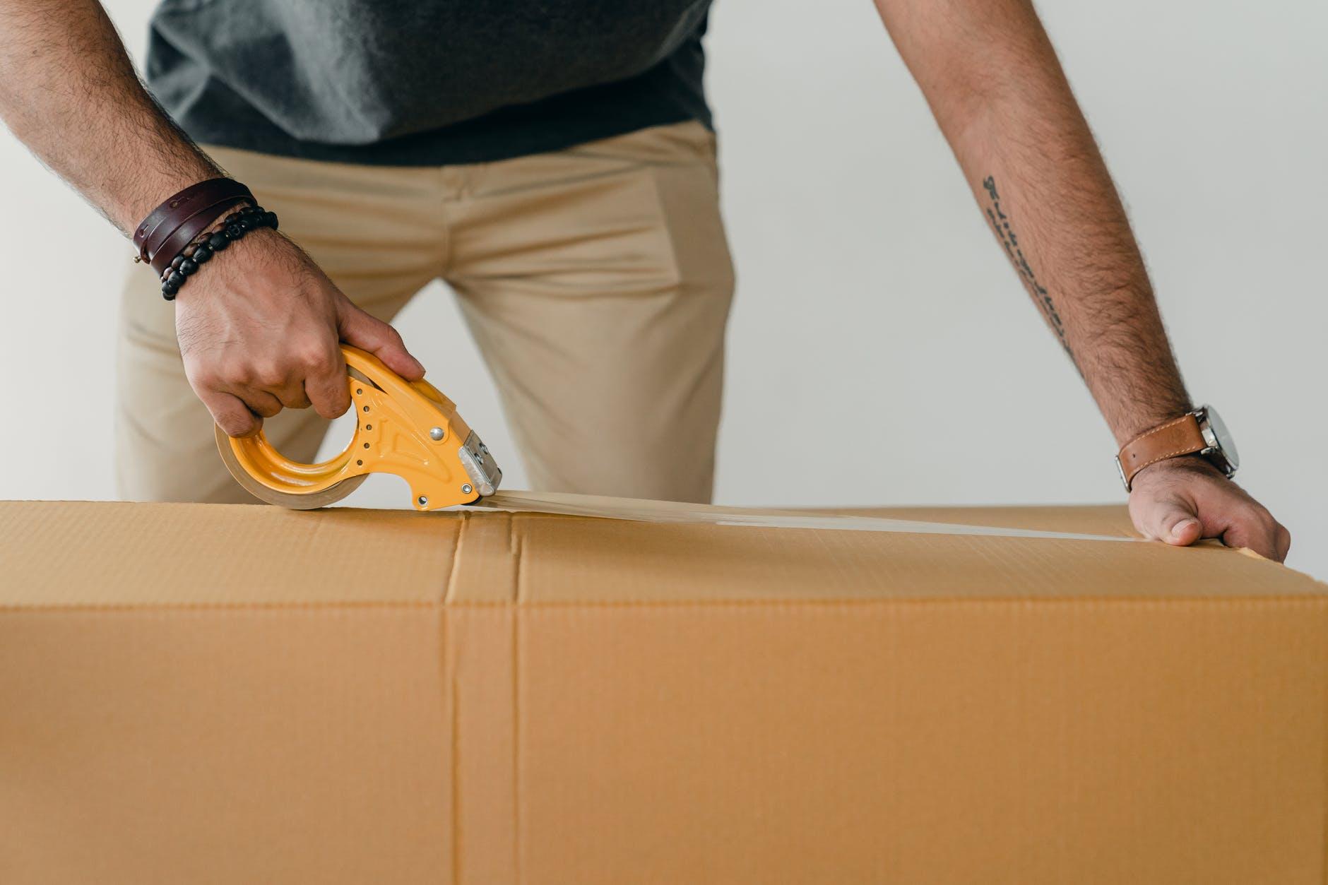 crop man sealing carton box with adhesive tape